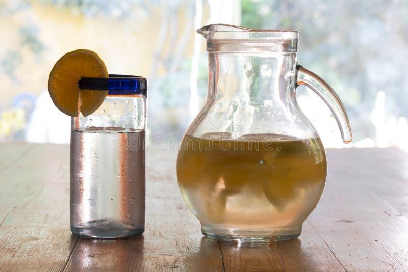 Oranje limonadeglas en waterkruik royalty-vrije stock foto's