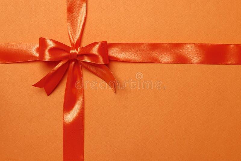 Oranje lint en boog op een oranje achtergrond royalty-vrije stock foto's