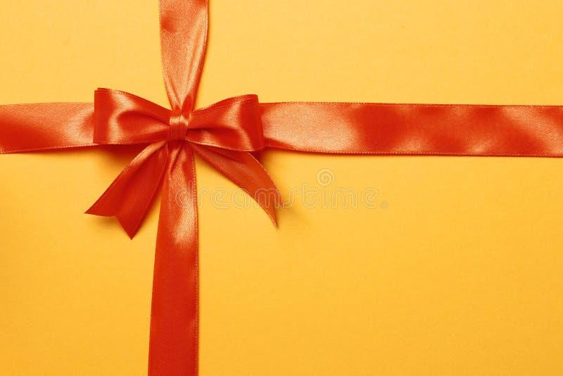 Oranje lint en boog op een oranje achtergrond stock afbeelding