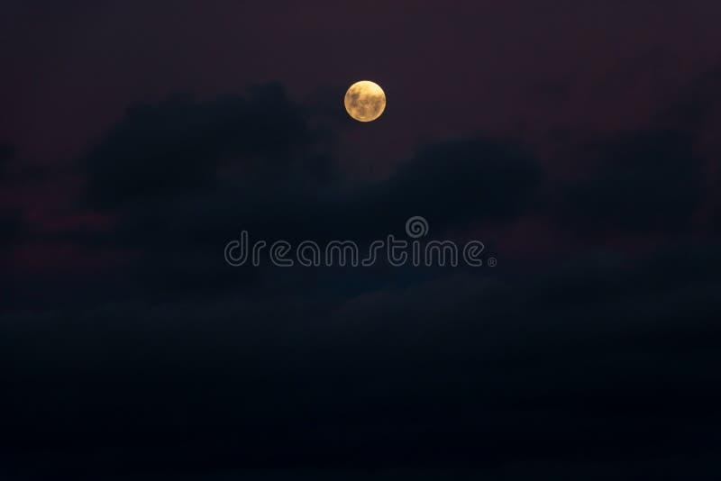 Oranje maan met purpere schemeringwolken stock foto's