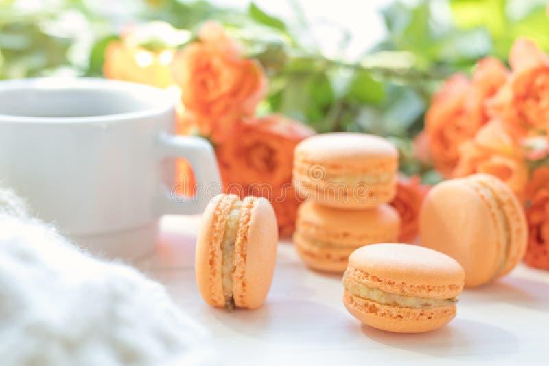 Oranje makarons, kop van koffie en verse rozen stock foto