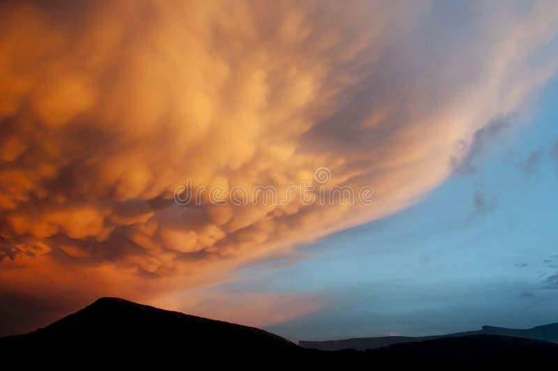 Oranje mammatuswolken bij de zonsondergang stock afbeelding