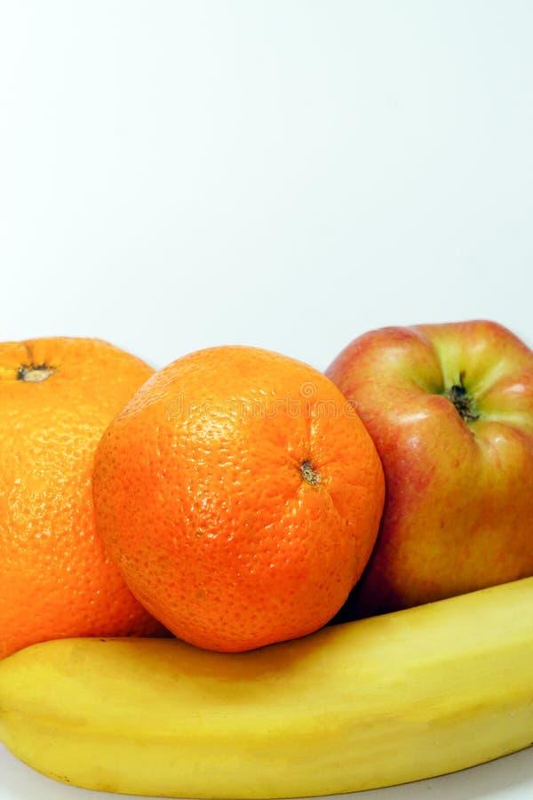 Oranje mandarin banaan en appel op wit geïsoleerde achtergrond stock foto