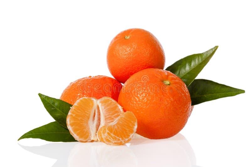 Oranje mandarines, de clementines, de mandarijnen of de kleine sinaasappelen met één pelden en besnoeiing in de helft met bladere royalty-vrije stock afbeeldingen