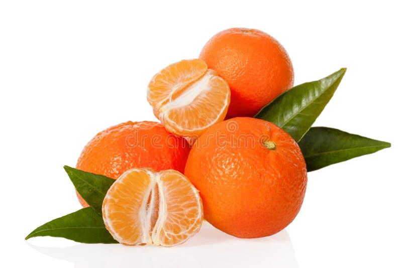 Oranje mandarines, de clementines, de mandarijnen of de kleine sinaasappelen met één pelden en besnoeiing in de helft met bladere royalty-vrije stock fotografie