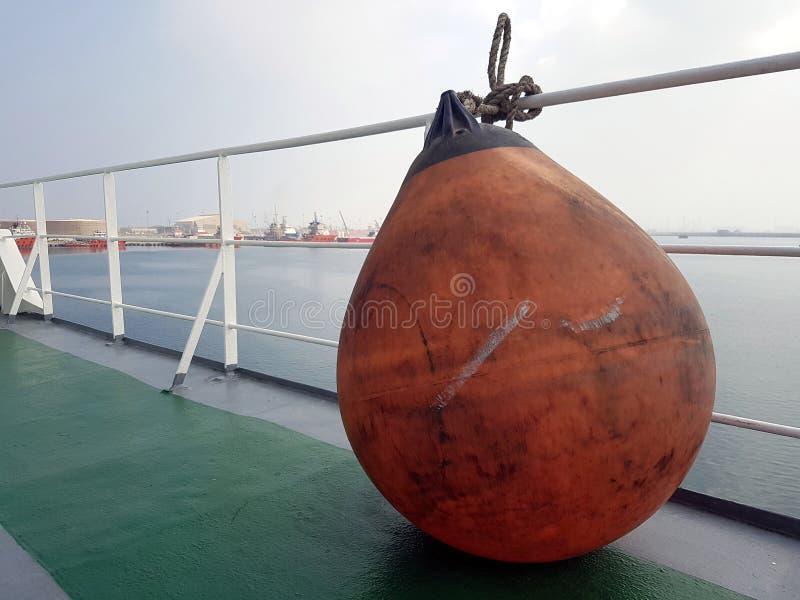 Oranje marien stootkussen op dek klaar om worden opgesteld om bootschil te beschermen royalty-vrije stock afbeelding