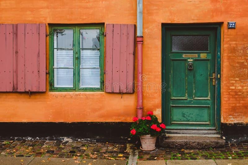Oranje Muur, Groene Vensters en Rode Bloempot royalty-vrije stock afbeelding