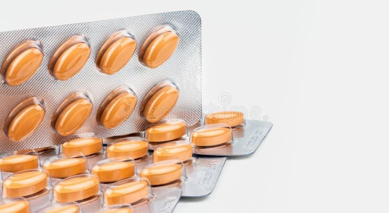 Oranje ovale die tabletpillen op witte achtergrond worden geïsoleerd Geneeskunde voor het behandelen van aderlijke omloopwanorde  stock afbeeldingen