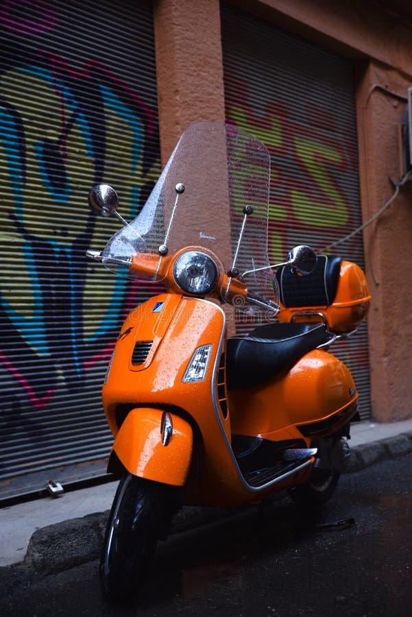 Oranje Piaggio Vespa stock afbeeldingen
