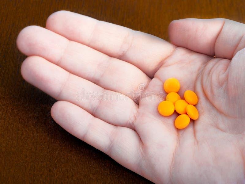 Oranje pillen op de palm van uw hand royalty-vrije stock foto