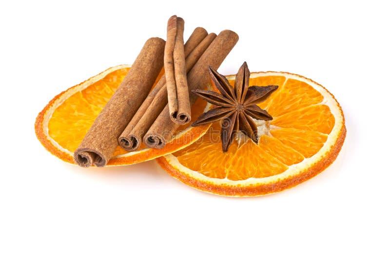 Oranje plakken, kaneel en anijsplant op wit royalty-vrije stock afbeeldingen