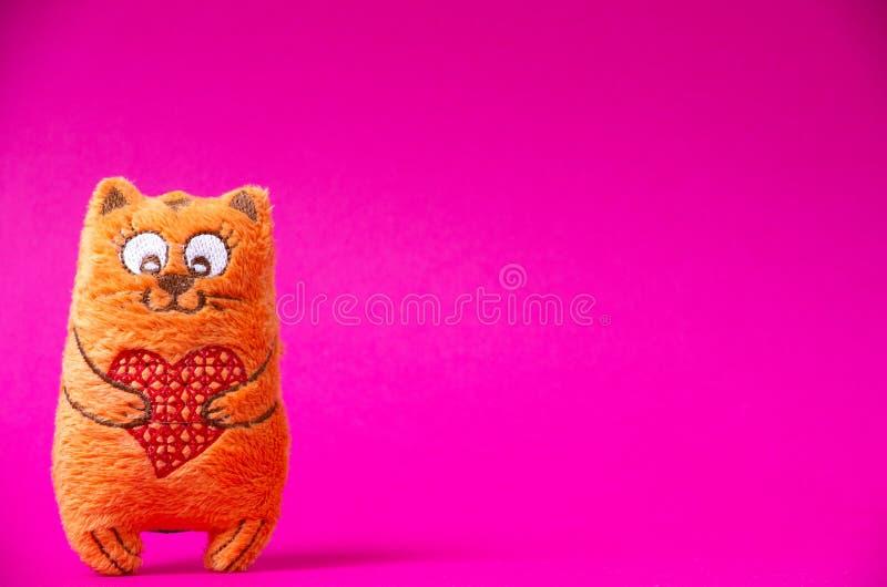 Oranje pluchekat met rood hart zo leuk op de roze achtergrond royalty-vrije stock foto