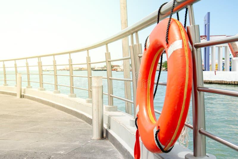 Oranje reddingsboei die bij het traliewerk van het dok wordt vastgelegd stock fotografie
