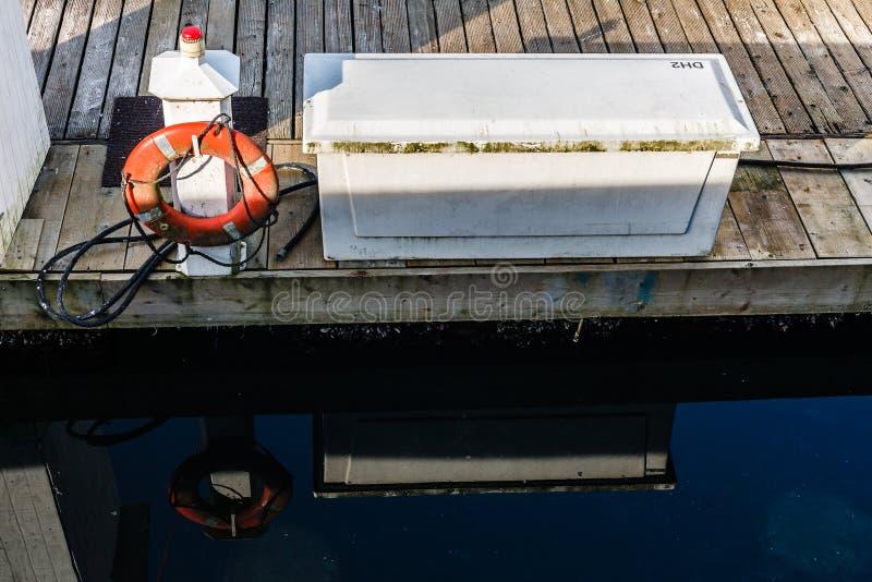 Oranje reddingsboei op de pijler en bezinning in het water stock foto's