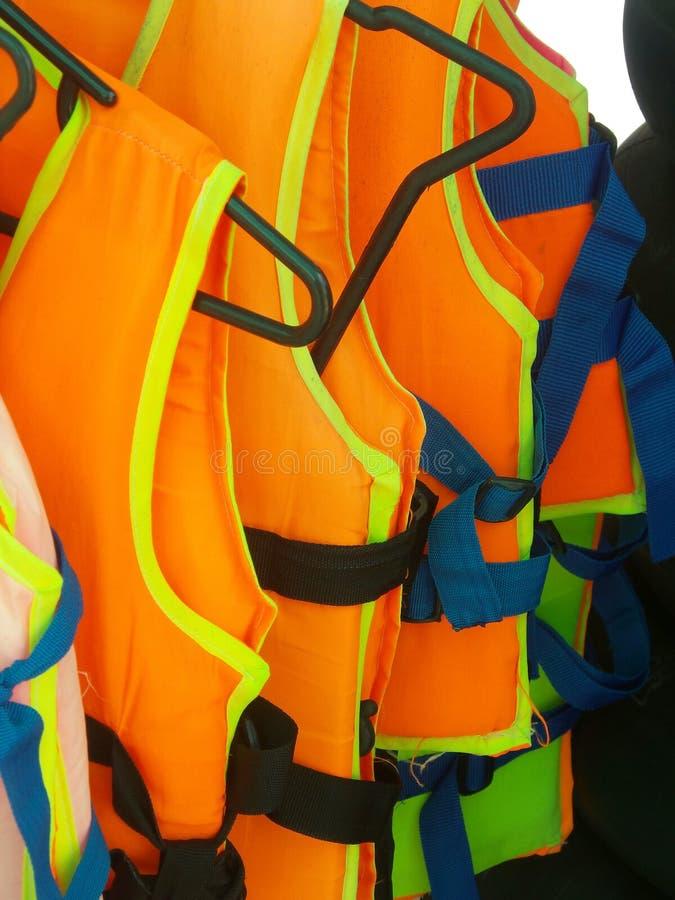 Oranje reddingsvest Oud reddings uitstekend meest lifevest voorwerp voor het veilige varen geïsoleerde op houten achtergrond stock afbeeldingen