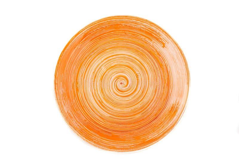 Oranje ronde ceramische plaat met spiraalvormig die patroon, op wit wordt geïsoleerd stock afbeelding