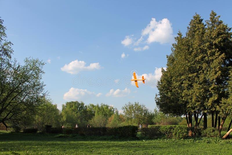 Oranje schuimvliegtuig die in de lucht tegen de achtergrond van witte wolken en blauwe hemel drijven stock foto