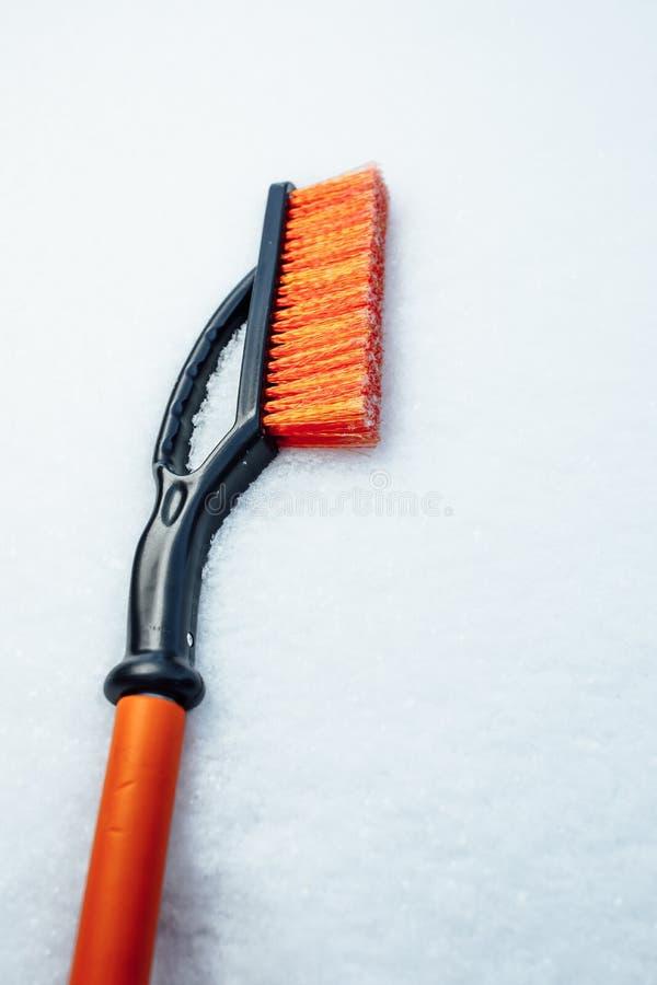 Oranje sneeuwborstel voor auto, sneeuwvlokkenachtergrond stock foto's