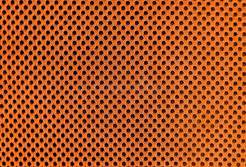 Oranje in te ademen poreus poriferous materiaal voor luchtventilatie met gaten Sportkledings materiële nylon textuur stock foto