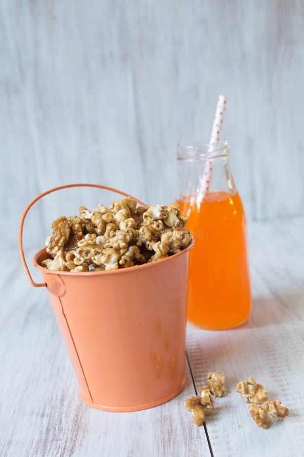Oranje Tin With Caramel Popcorn en Frisdrank stock foto's