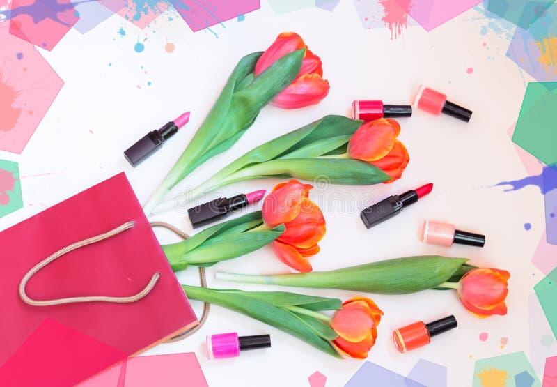 Oranje tulpen, kleurrijke nagellakken en lippenstiften in document zak op pastelkleurachtergrond stock afbeeldingen