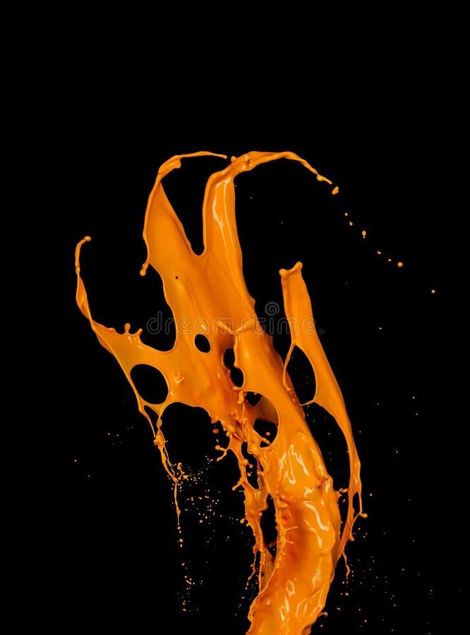 Oranje verfplons op zwarte achtergrond stock afbeelding