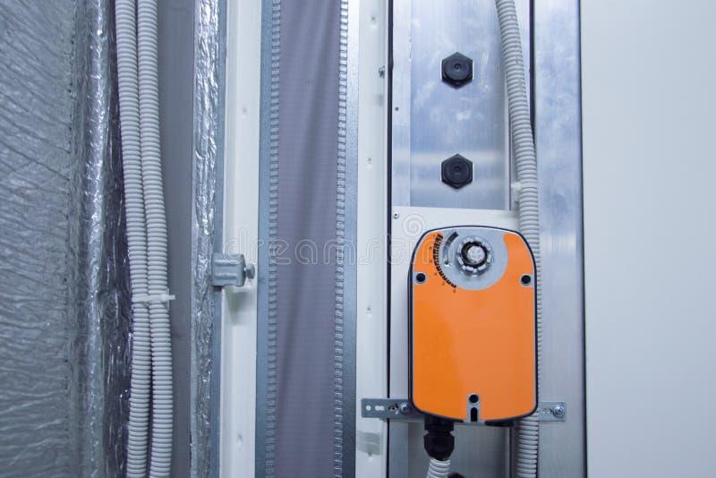 Oranje vochtigere actuator die op het industriële lichaam van de ventilatieeenheid, vooraanzicht wordt geïnstalleerd royalty-vrije stock fotografie