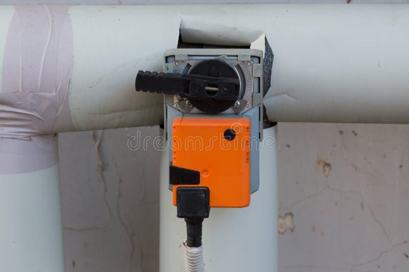 Oranje vochtigere actuator die op het industriële lichaam van de ventilatieeenheid, vooraanzicht wordt geïnstalleerd stock foto's