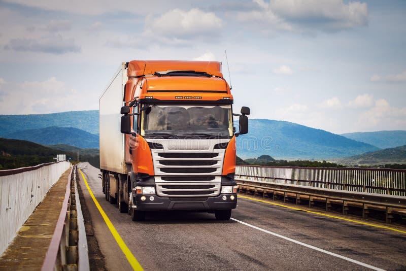 Oranje vrachtwagen op een weg stock foto's