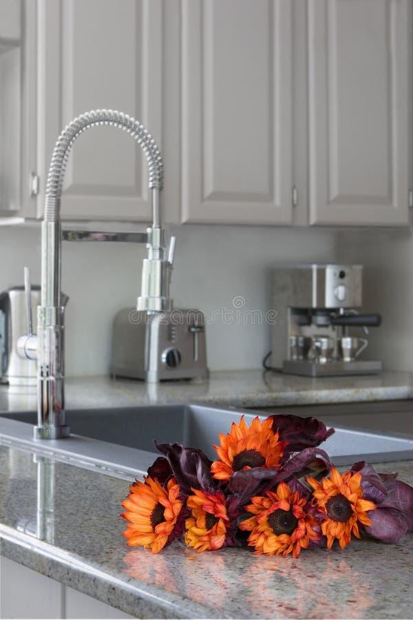 Oranje zonnebloemen op een moderne keukenteller royalty-vrije stock afbeeldingen
