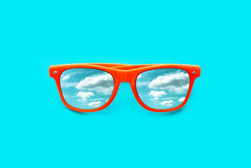 Oranje zonnebril met blauwe die hemel met wolkenbezinningen op intense cyaan blauwe achtergrond worden geïsoleerd stock afbeeldingen