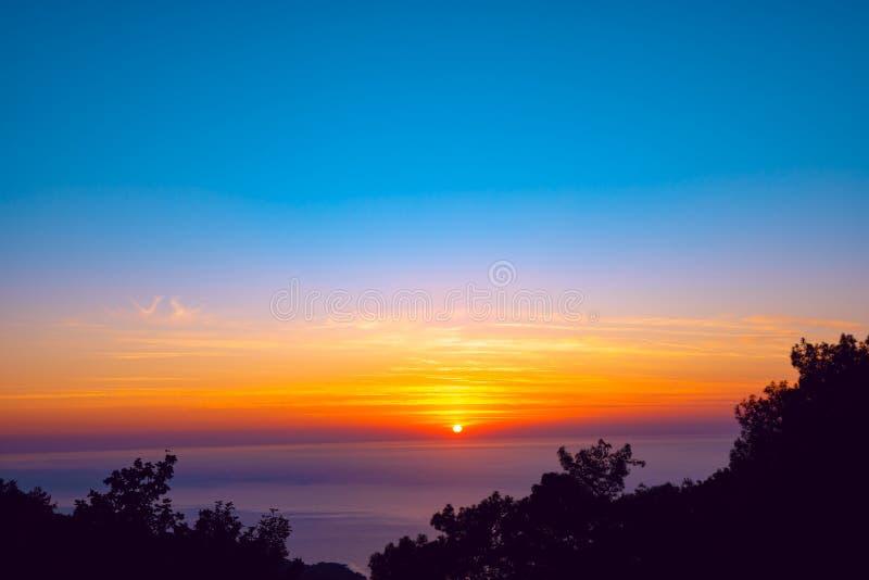 Oranje zonreeksen op de horizon over het purpere overzees royalty-vrije stock foto's
