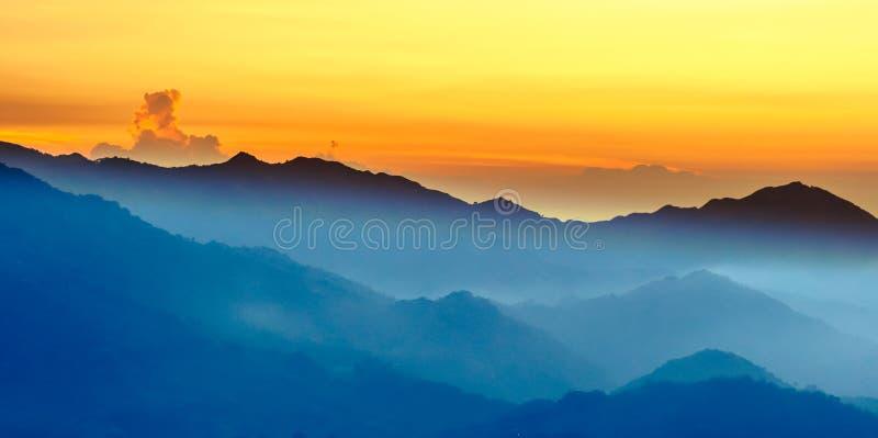 Oranje zonsondergang in de bergen stock fotografie