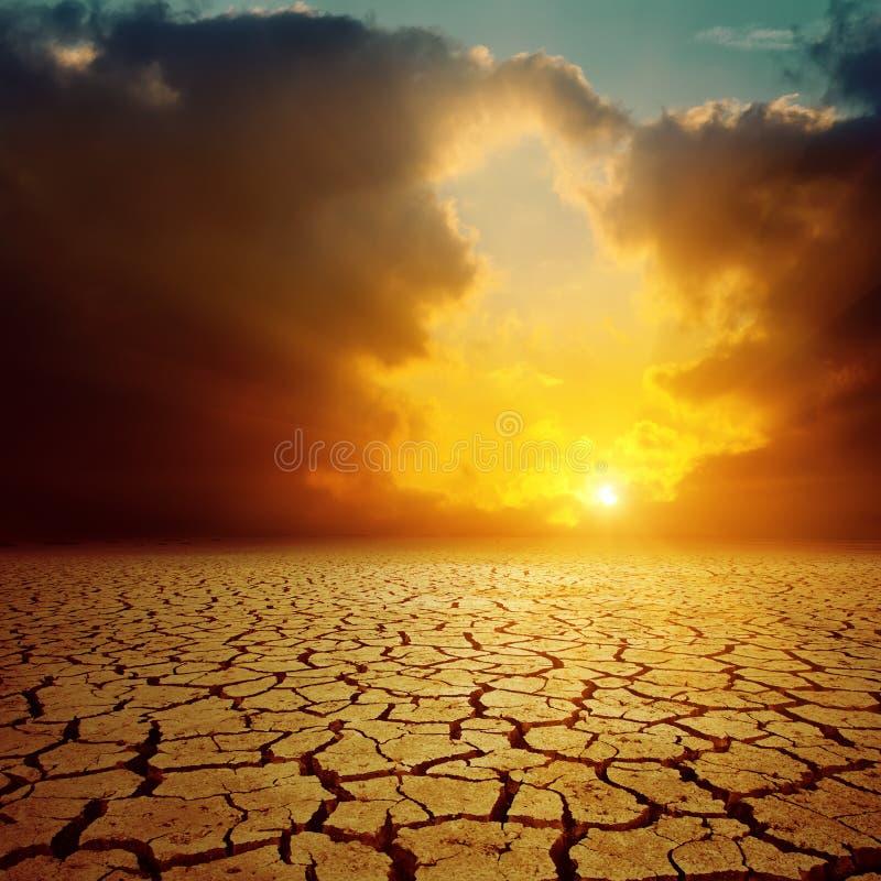 Oranje zonsondergang over gebarsten woestijn stock fotografie