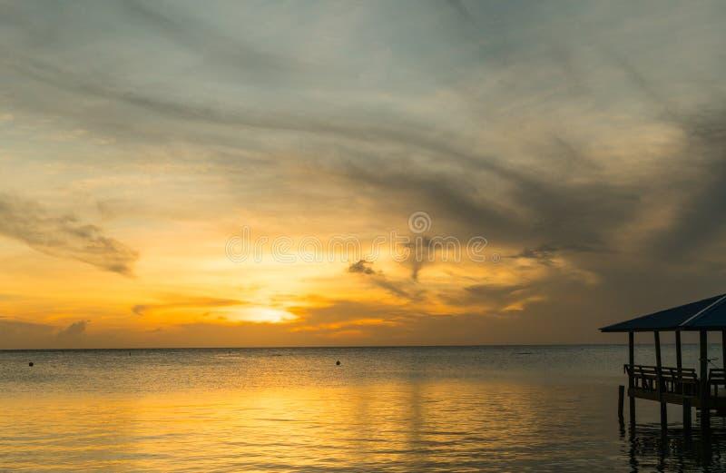 Oranje zonsonderganghemel over de oceaan met een dok stock afbeelding