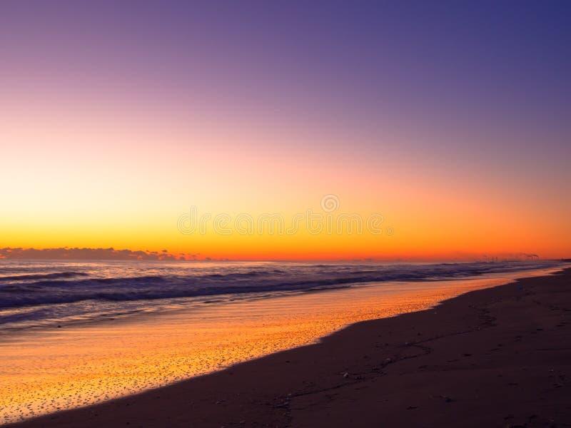 Oranje zonsopgangkleur op de lange strandlijn stock foto's