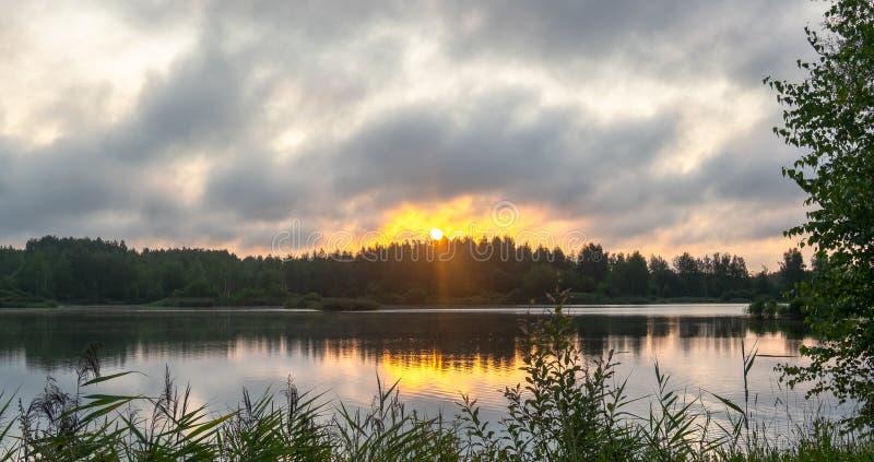 Oranjegele zonsopgang door een sterke wolk over het meer royalty-vrije stock afbeeldingen