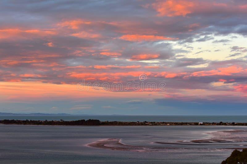 Oranjerode die wolken door de het plaatsen zon in Avon Heathcote Estuary in Christchurch worden veroorzaakt stock afbeelding