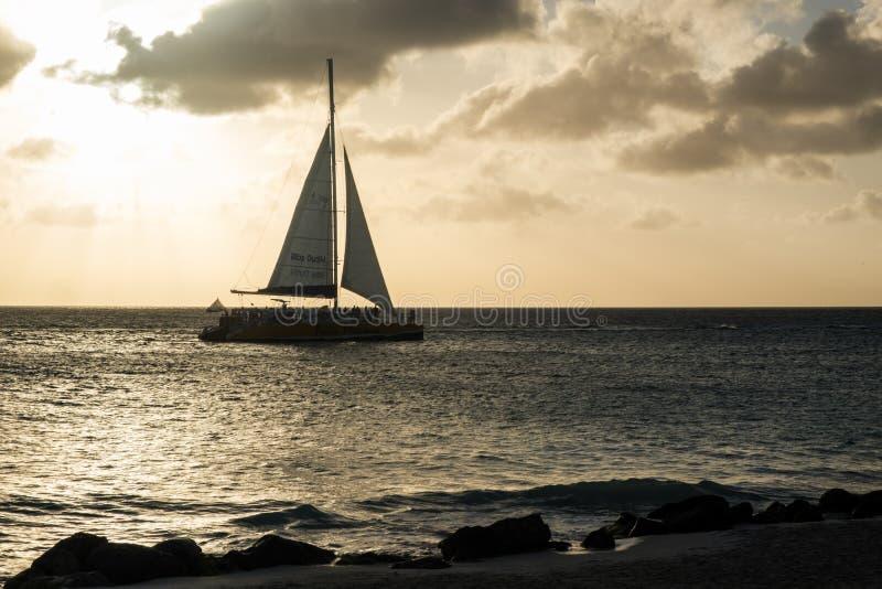 Oranjestad, Αρούμπα - 10 Απριλίου 2018: ναυσιπλοΐα sailboat κοντά στην παραλία αετών στο ηλιοβασίλεμα στοκ εικόνα