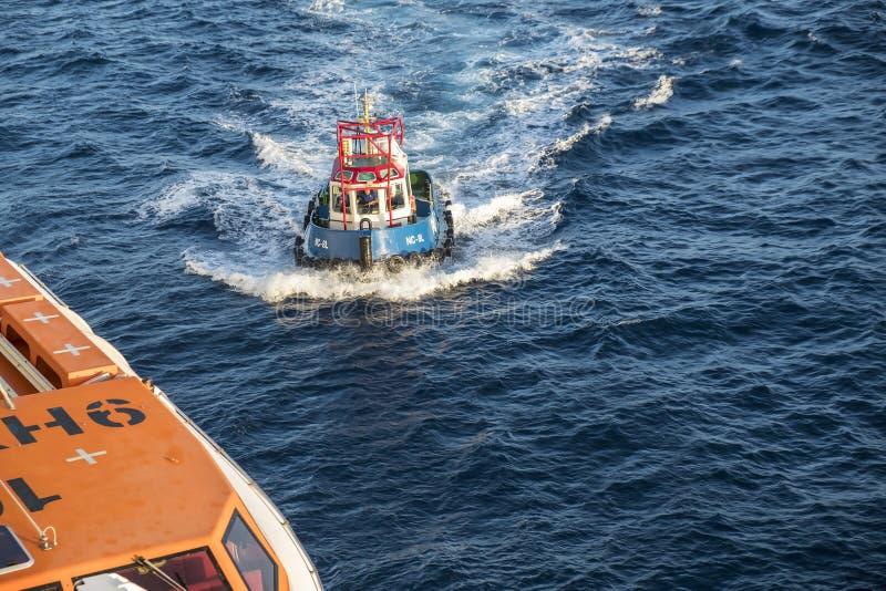 Oranjestad, Aruba - April 10, 2018: Pilot boat guiding cruise ship to the shore royalty free stock photos