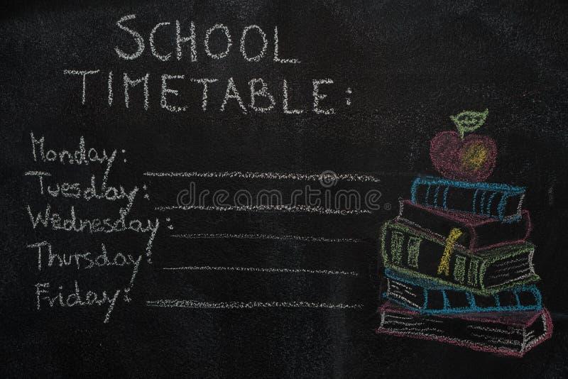 Orario della scuola e pila di libri con la lavagna nera attinta mela fotografia stock libera da diritti