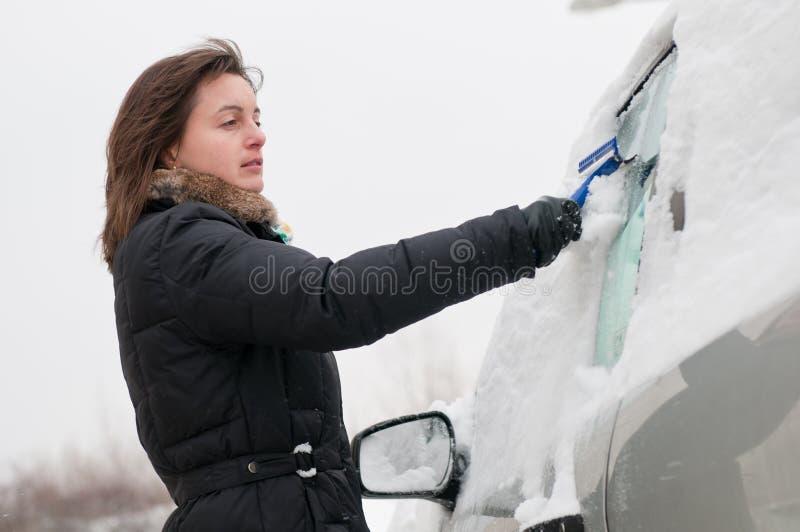 Orario invernale - automobile di pulizia della persona fotografia stock