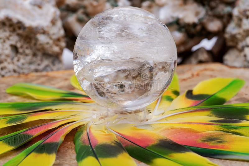 Orb för kristall för sfär för Lemurian frikändkvarts magisk i mitt av en cirkel som göras av färgrika fjädrar royaltyfria bilder