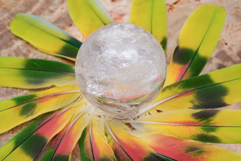 Orb för kristall för sfär för Lemurian frikändkvarts magisk i mitt av en cirkel som göras av färgrika fjädrar royaltyfri bild