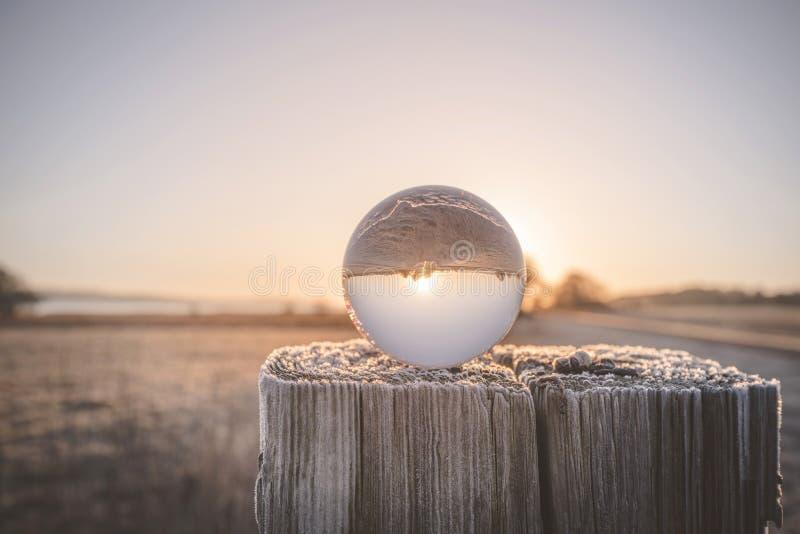 Orbe de cristal en un poste de madera en la salida del sol imágenes de archivo libres de regalías