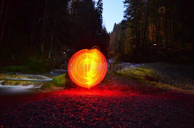 Orbe rojo que brilla intensamente al lado de la cascada imágenes de archivo libres de regalías
