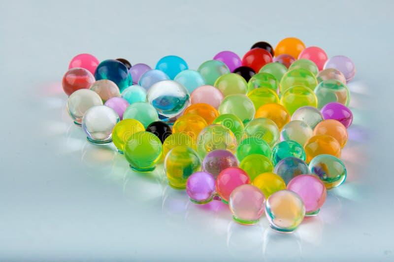 Orbeez放置在心脏的水凝胶球在白色背景塑造 免版税库存图片