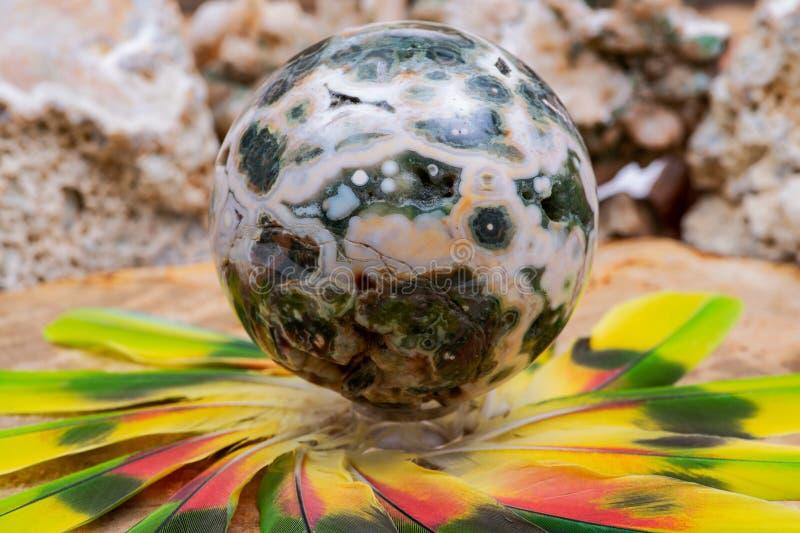 Orbicular Oceaanjaspisgebied met gekristalliseerd die vugs van Madagascar in het midden van een cirkel van kleurrijke veren wordt stock afbeelding