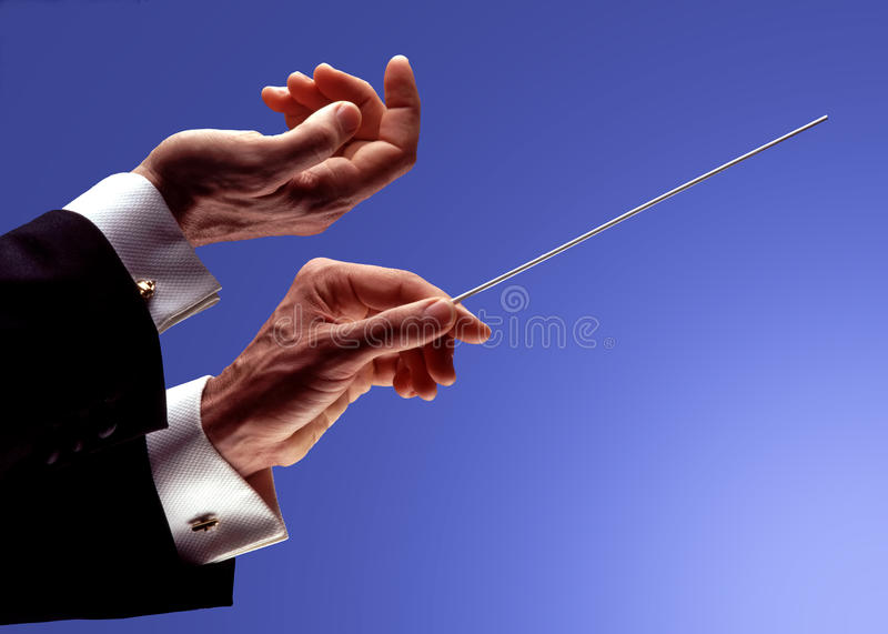 Orchestra conductor hands. On a graduate blue back stock photo