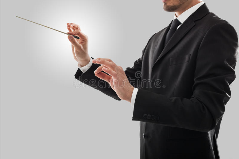 Orchestra leader. Orchestra conductor directing with his baton royalty free stock images